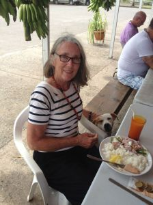 18. This is a photo of Anne with a new friend from Nuku Hiva, un petite chien (a little dog), sharing the most popular food on Nuku Hiva, the delicious Poisson Cru au Lait de Coco (that's French for Raw fish with and coconut milk).  They also add fresh Nuku Hivan lime juice!