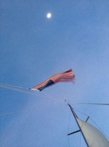 30. Joyful's United States of America ensign flying on her backstay, highlighted by the full moon.