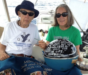 38. Before deploying the NOAA drifter buoy, Jeff and Anne posed with the buoy, with the Bible verse John 8-12 painted on the top surface, and the Mission Joyful blanket given to them by the congregation of the Huntsville First United Methodist Chapel.