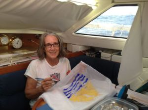 57. Anne used acrylic paint on thin white fabric to paint a French Polynesian courtesy flag for Joyful.  To show courtesy, foreign boats should fly the host nation's flag from the starboard spreader halyard.