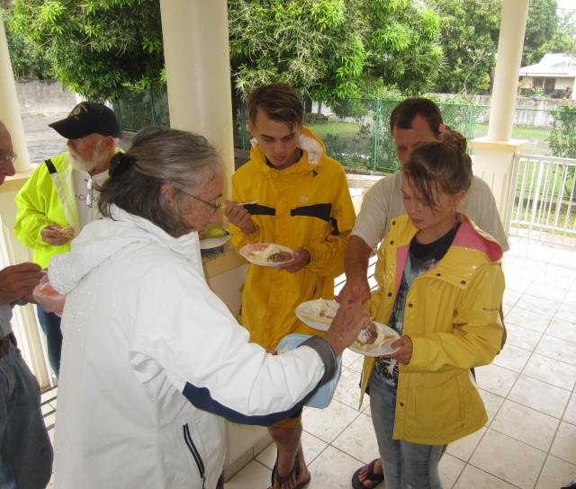 48. To celebrate the 4th of July, Anne serves Sailors for Christ friends a banana split.  Because of a rain storm the picnic was enjoyed under the front porch of a Bora Bora bank.